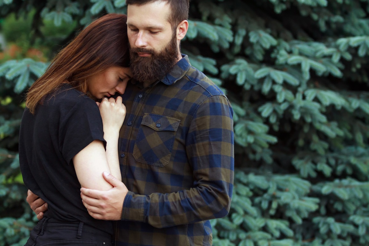 Man comforting sad woman in park