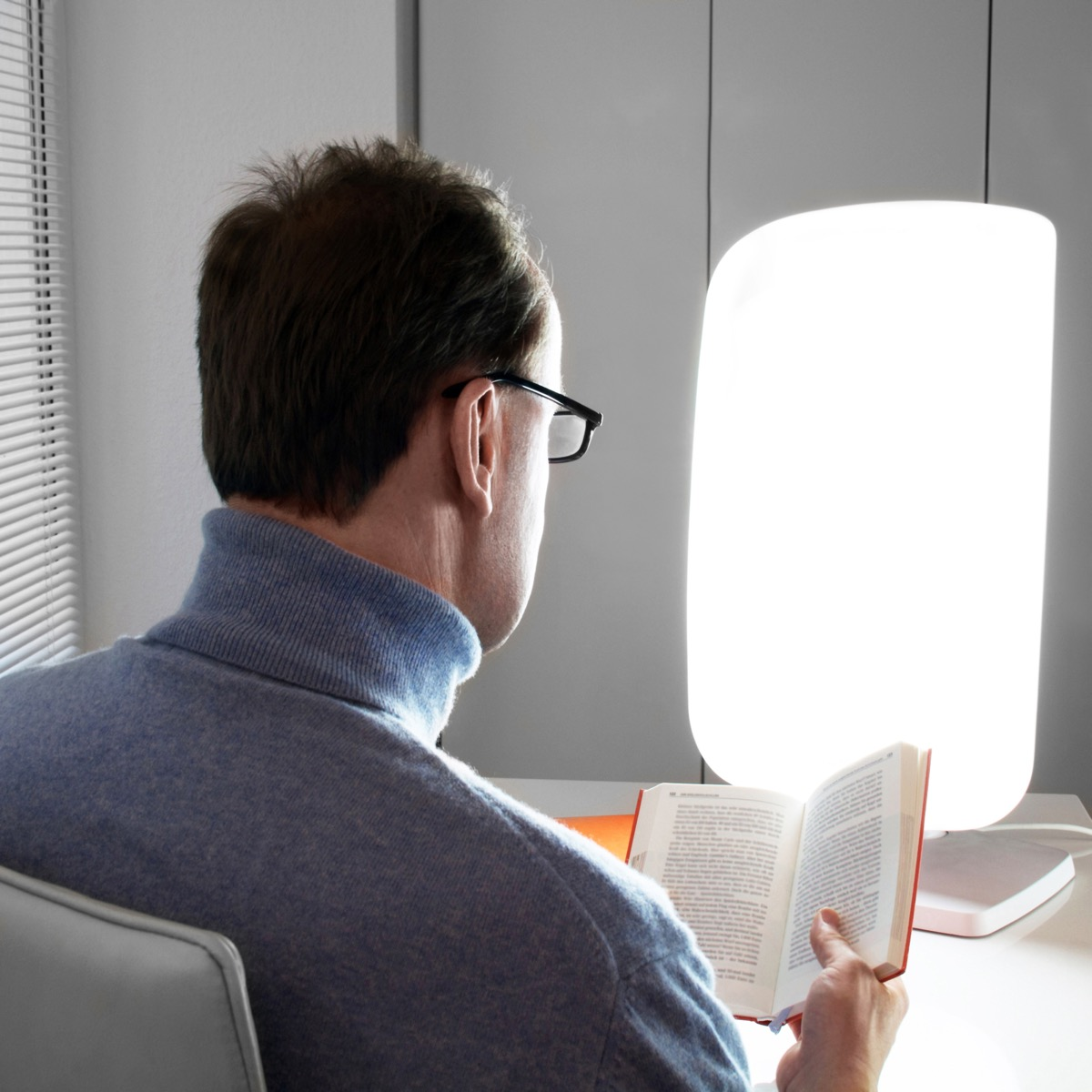Man using a bright light to beat the winter blues