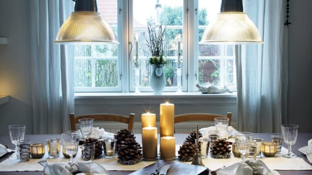 Dinner table ready for christmas dinner with pinecones and candles