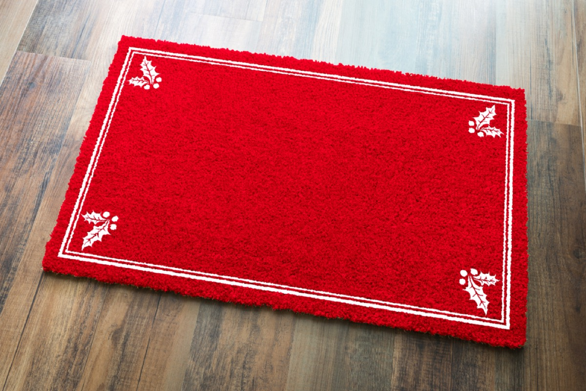 red welcome mat on wood floor with white holly leaves in corners
