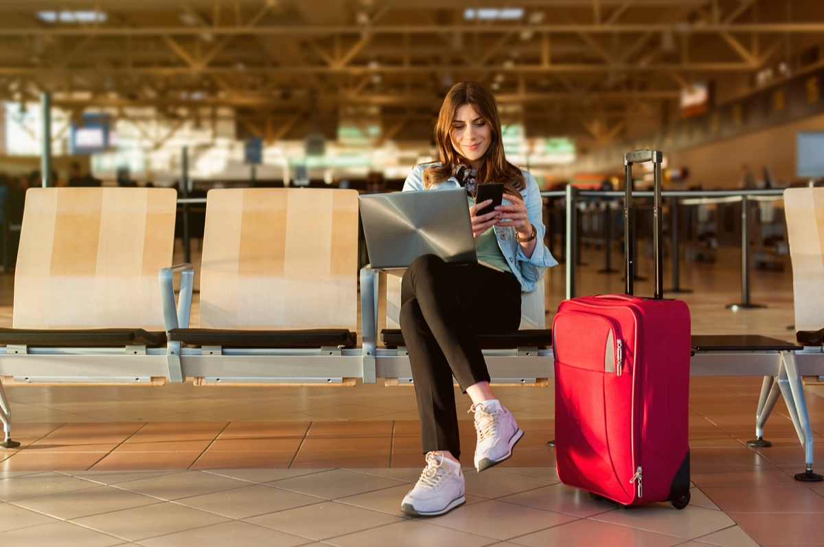 Woman Sitting at the Airport Waiting to Travel booking cheap flights