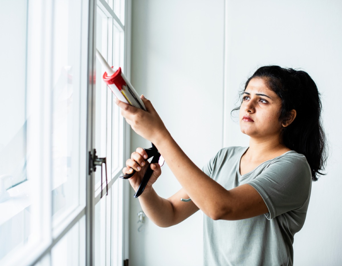 young woman caulks around windows