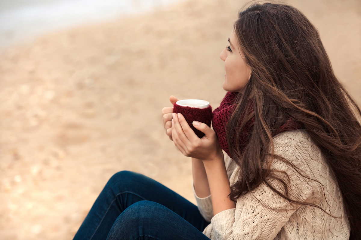 Woman drinking coffee on the beach christmas depression