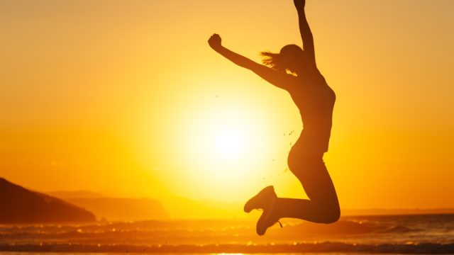 woman jumping into air on beach at sunset, monday quotes