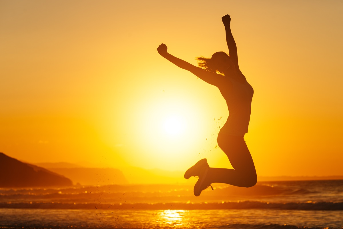 woman jumping into air on beach at sunset because she decided to delete instagram