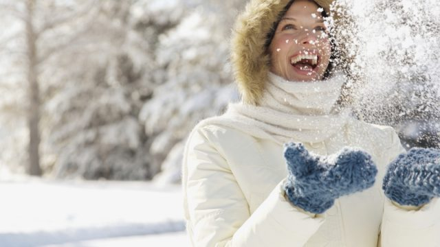 woman laughing in the snow - winter blues