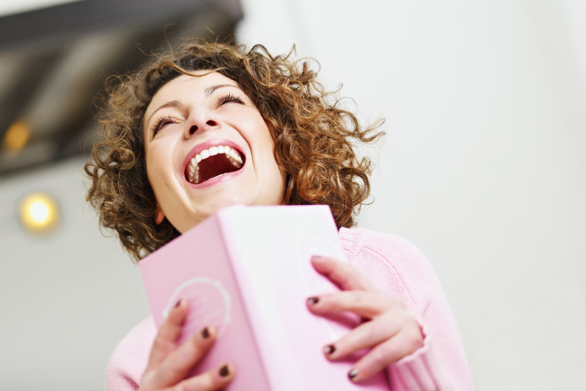 woman laughing while reading a book -- funny books