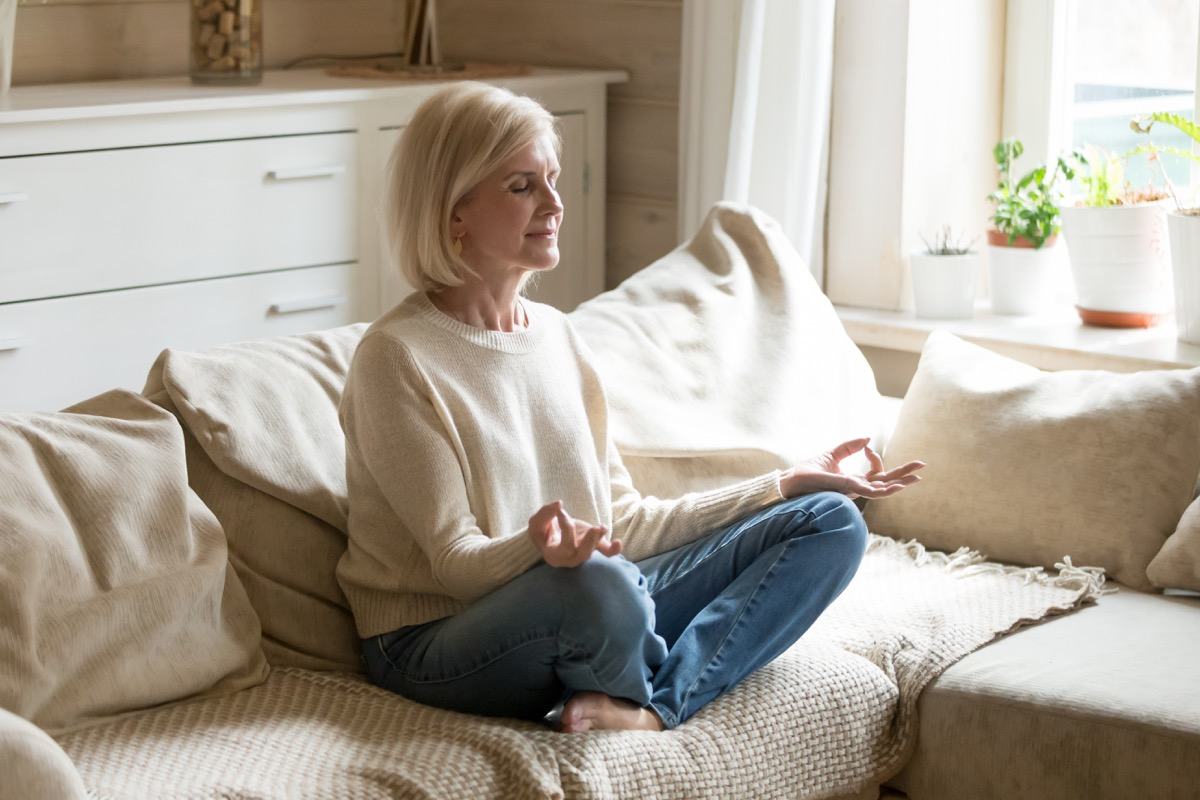 Woman meditating on her couch
