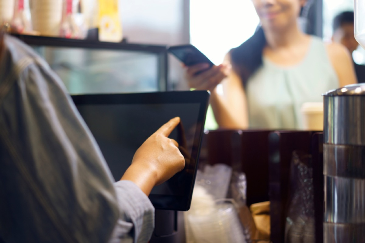 woman on phone ordering from cashier, rude behavior