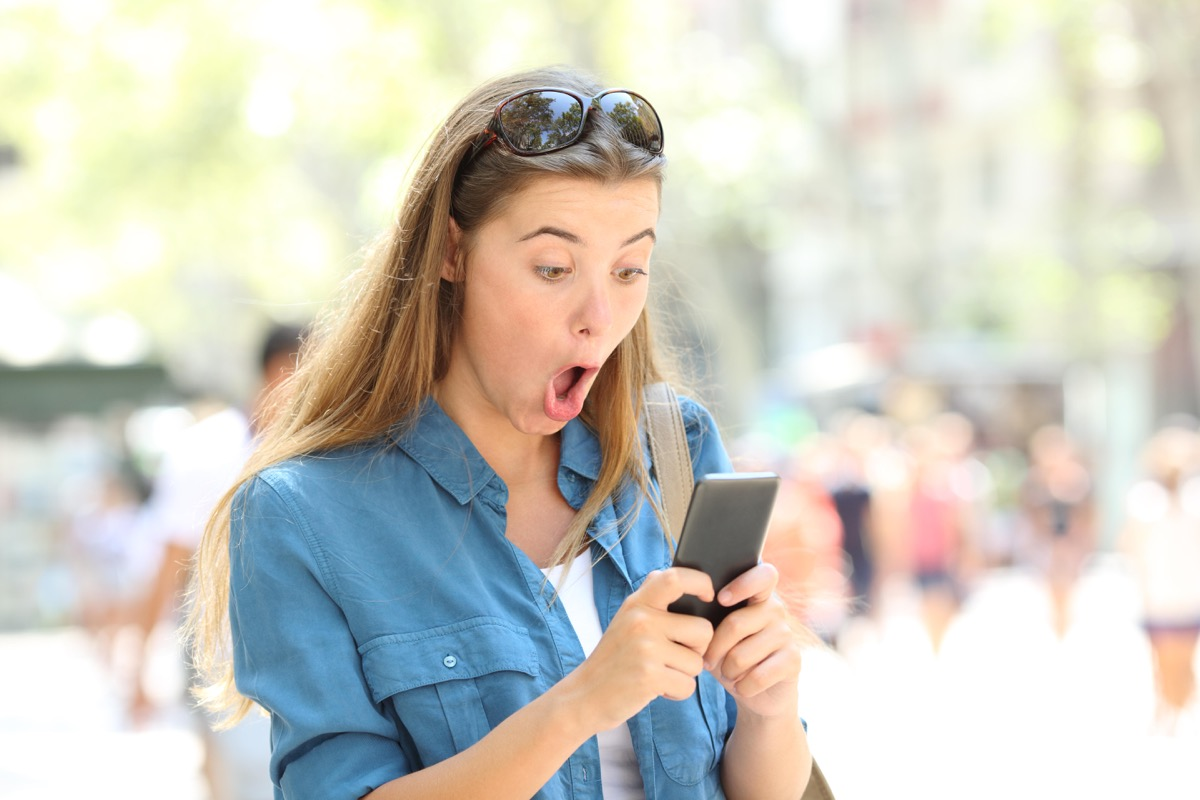 Woman on phone surprised reading viral dating story