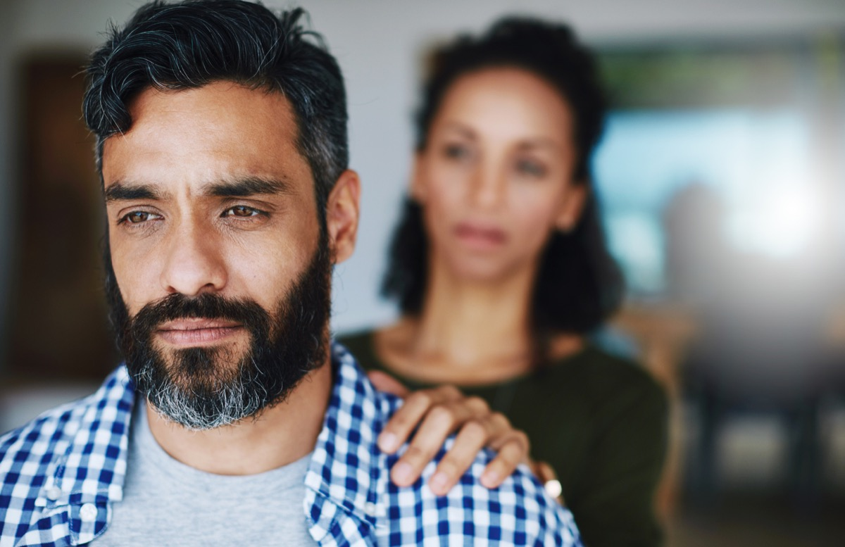 Shot of a woman comforting her distraught husband at home by putting her hand on his shoulder