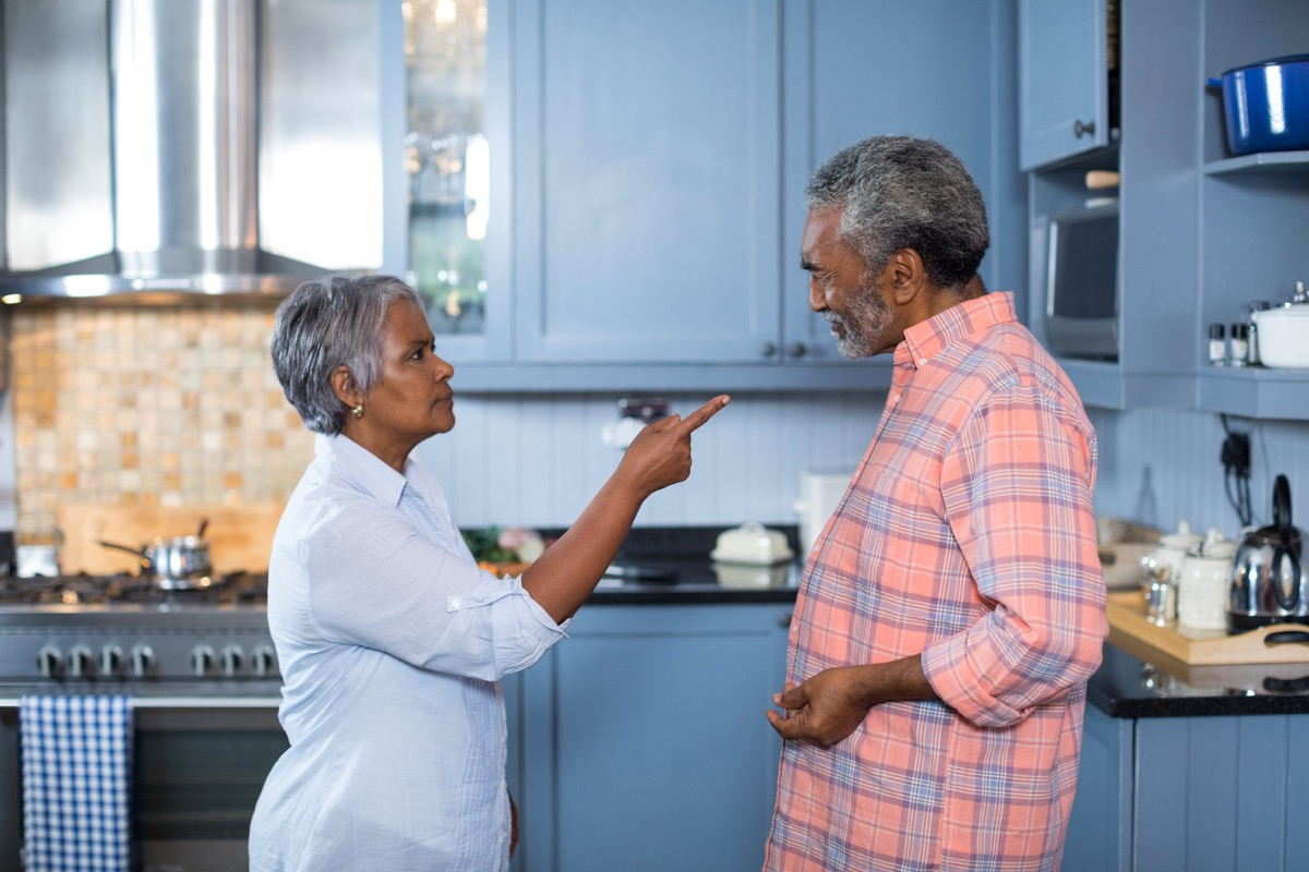 Unhappy senior black couple standing in kitchen while wife points finger