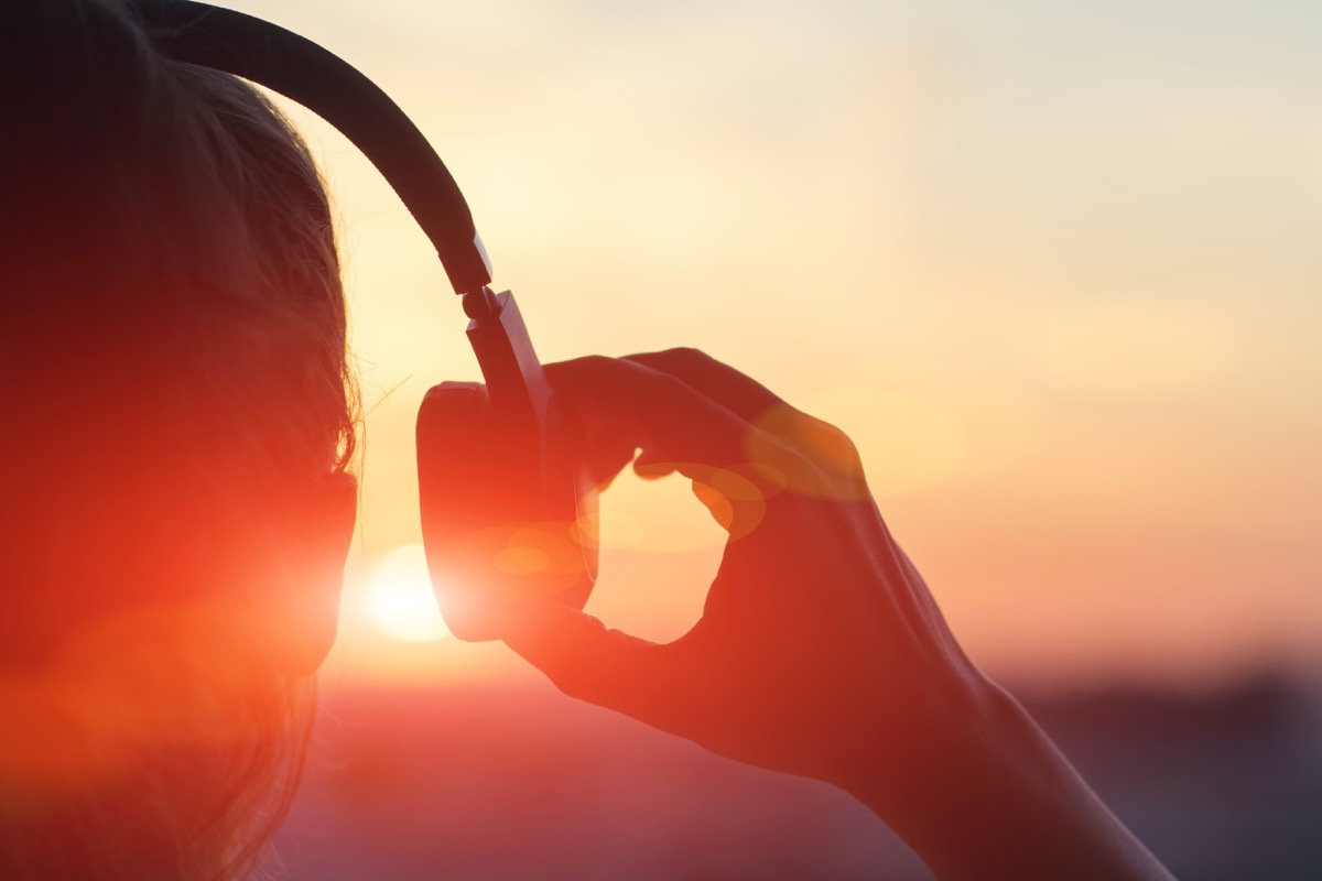 woman putting on over-ear headphones at sunset - sound facts