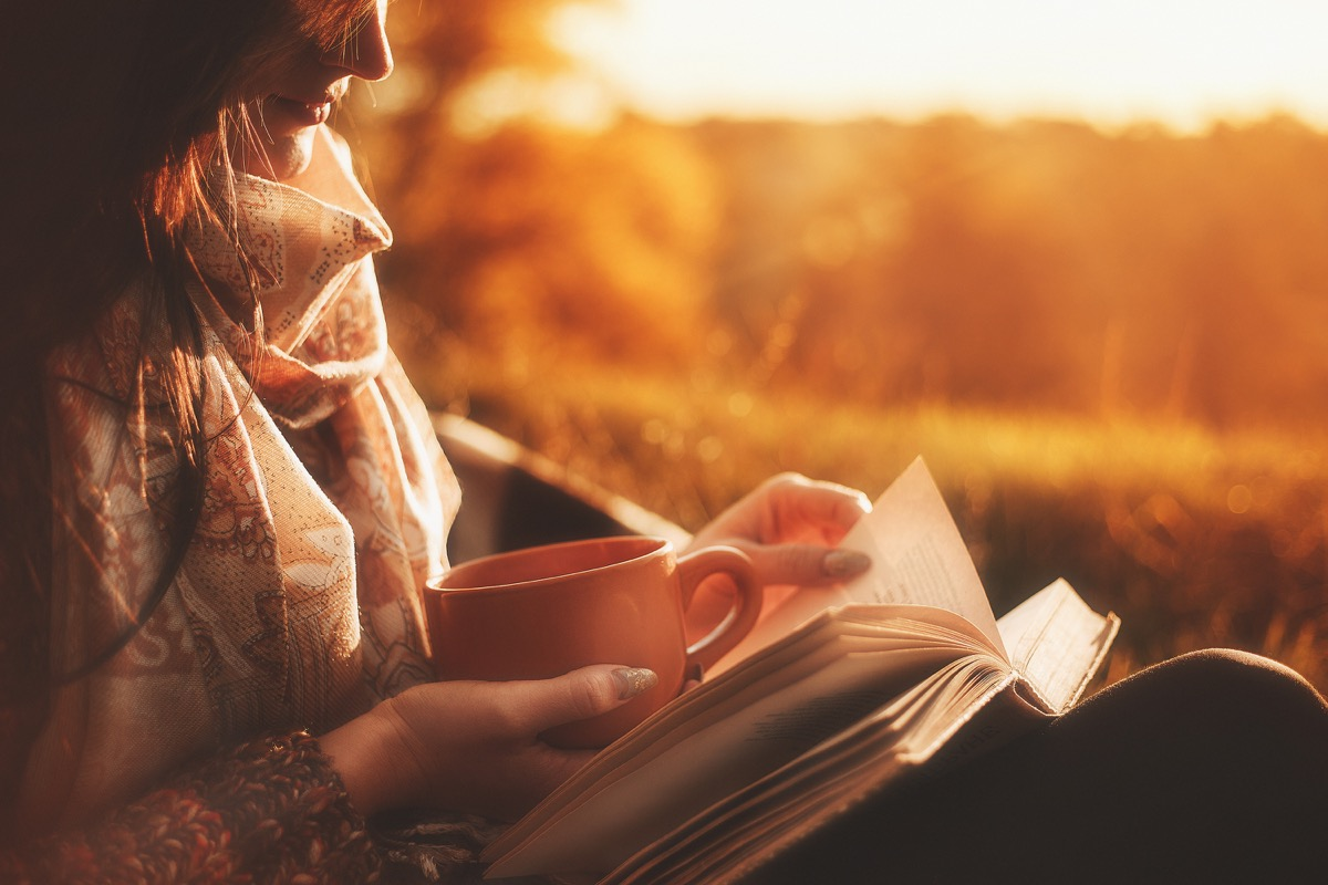 woman reading a book outside at sunset holding a cup of coffee christmas depression