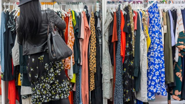 woman shops through rack of clothing