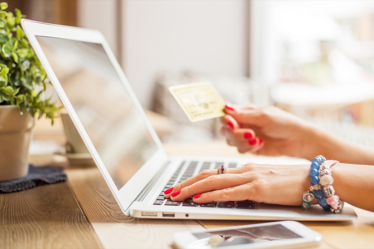 woman shopping online with a laptop and a credit card booking cheap flights