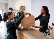 Woman shopping at checking out at the store with a cashier