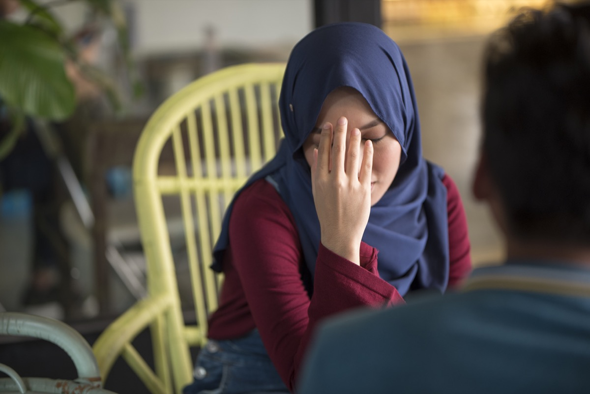 Young Muslim woman upset, holds head in hand