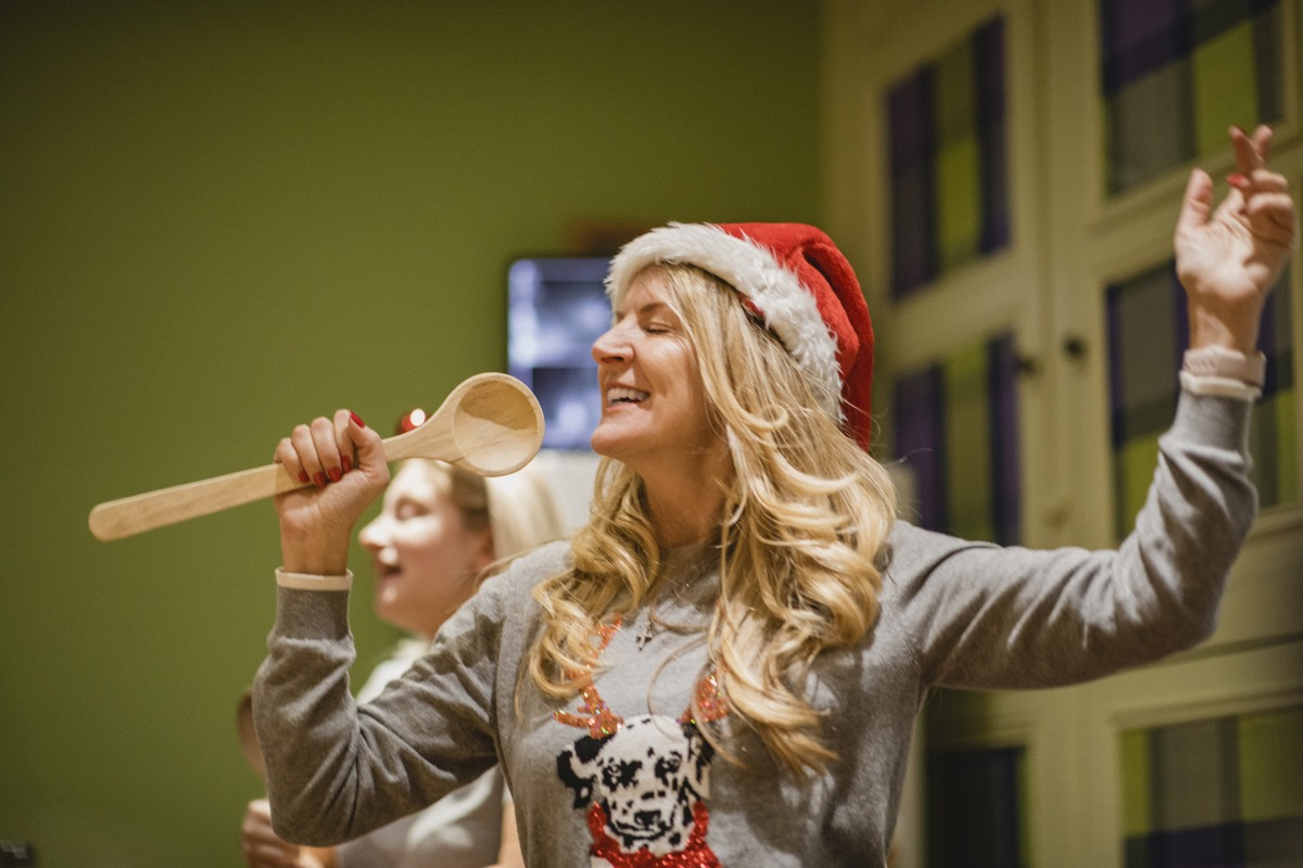 woman singing into a wooden spoon at a holiday party
