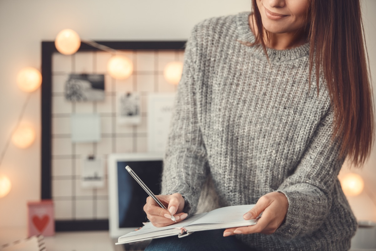 woman wearing sweater working in home office, ways parenting has changed.