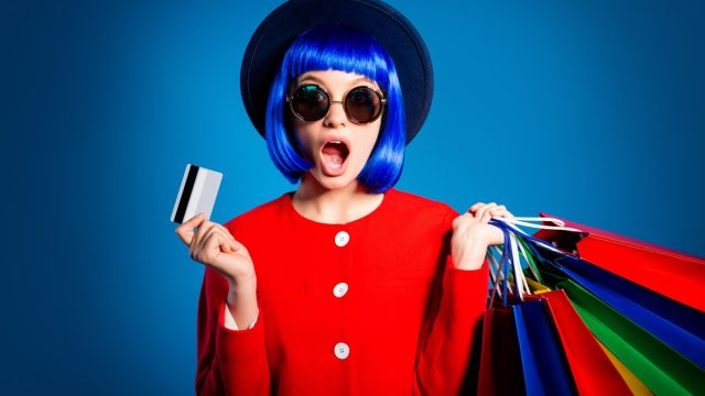 woman with shopping bags blue hair and a hat against a blue background
