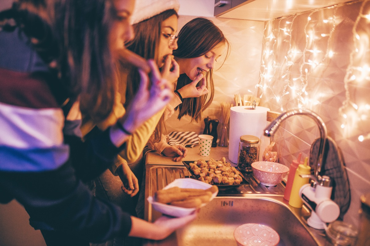 women eating chicken at a holiday party