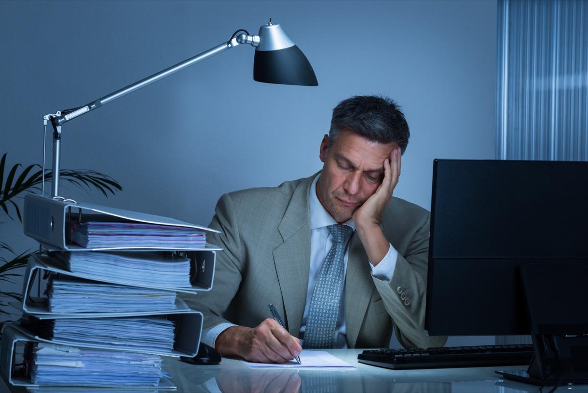 Man Writing at His Desk Feeling Sad Signs of Burnout