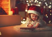 young child writing santa claus a letter in front of a christmas tree