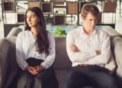 Resentful young man and woman look away from each other on couch