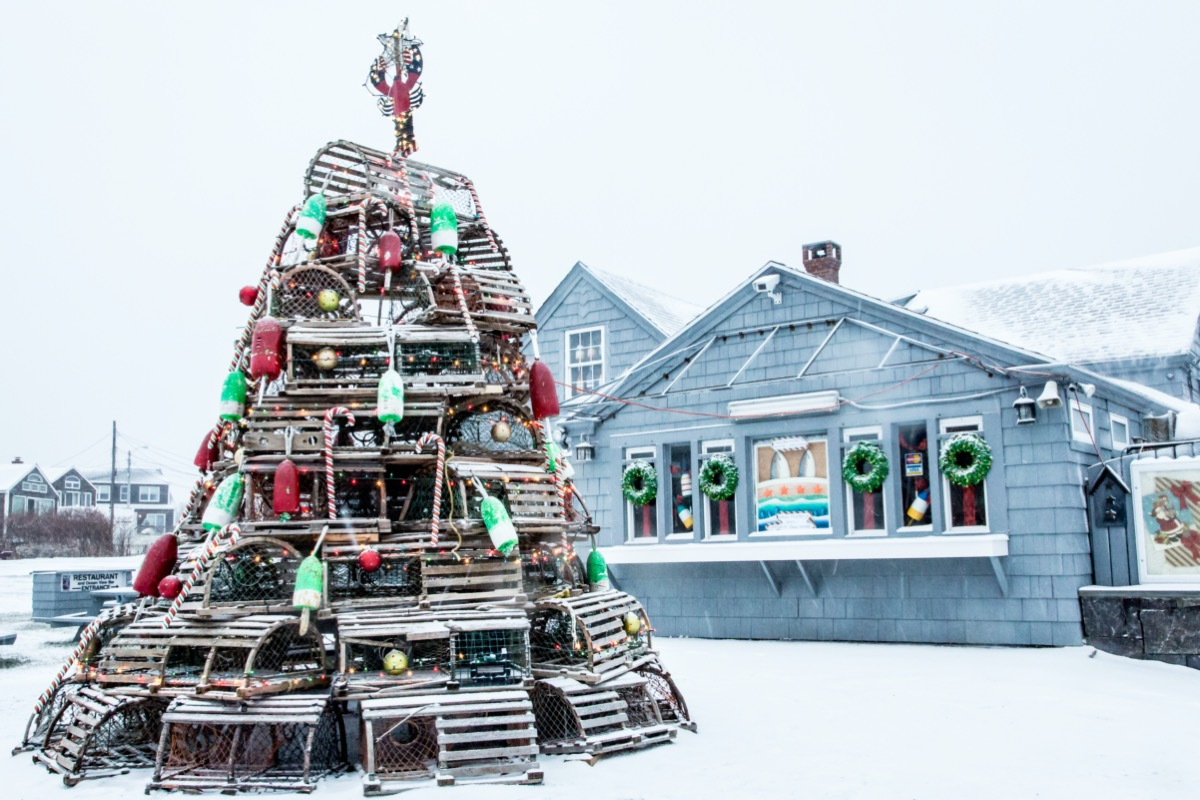 a christmas tree made out of lobster traps and buoys in front of a Maine seafood shack on a snowy day