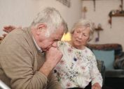 senior man with wife at home coughing badly, signs your cold is more serious