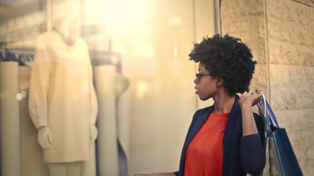 young black woman looking in store window