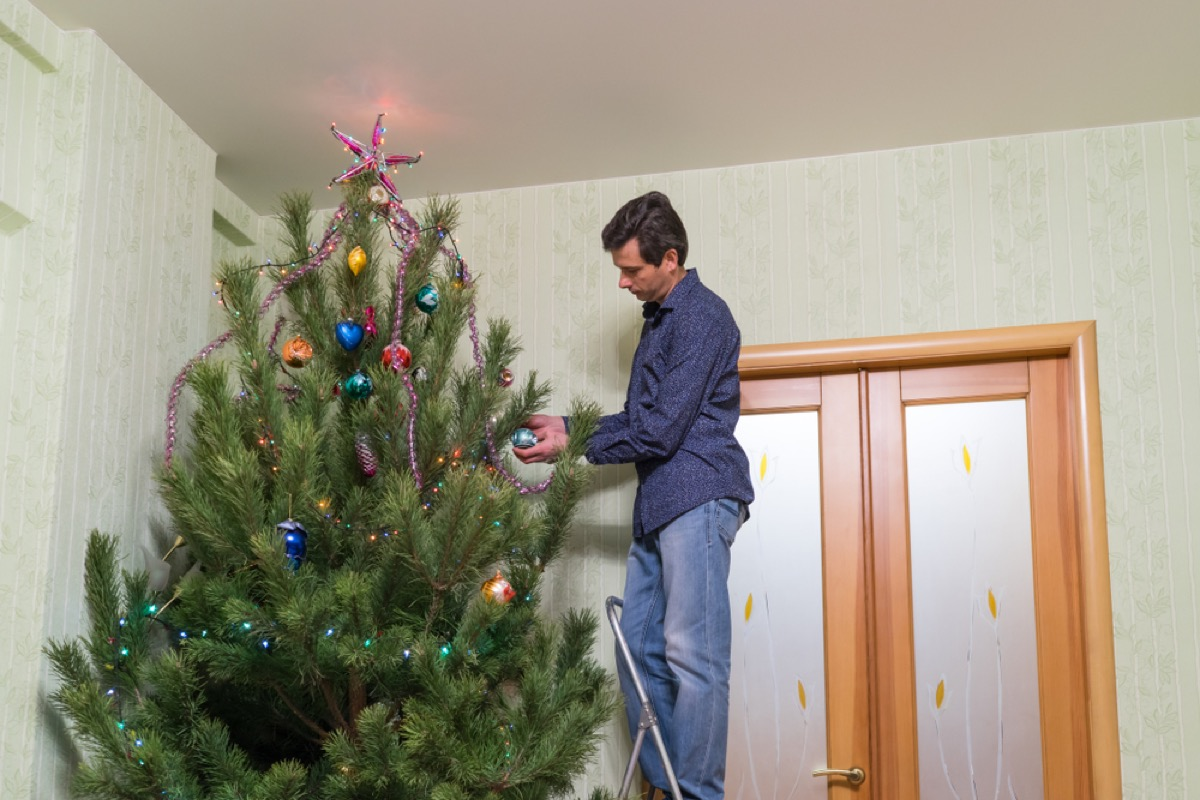 man standing on ladder to decorate christmas tree