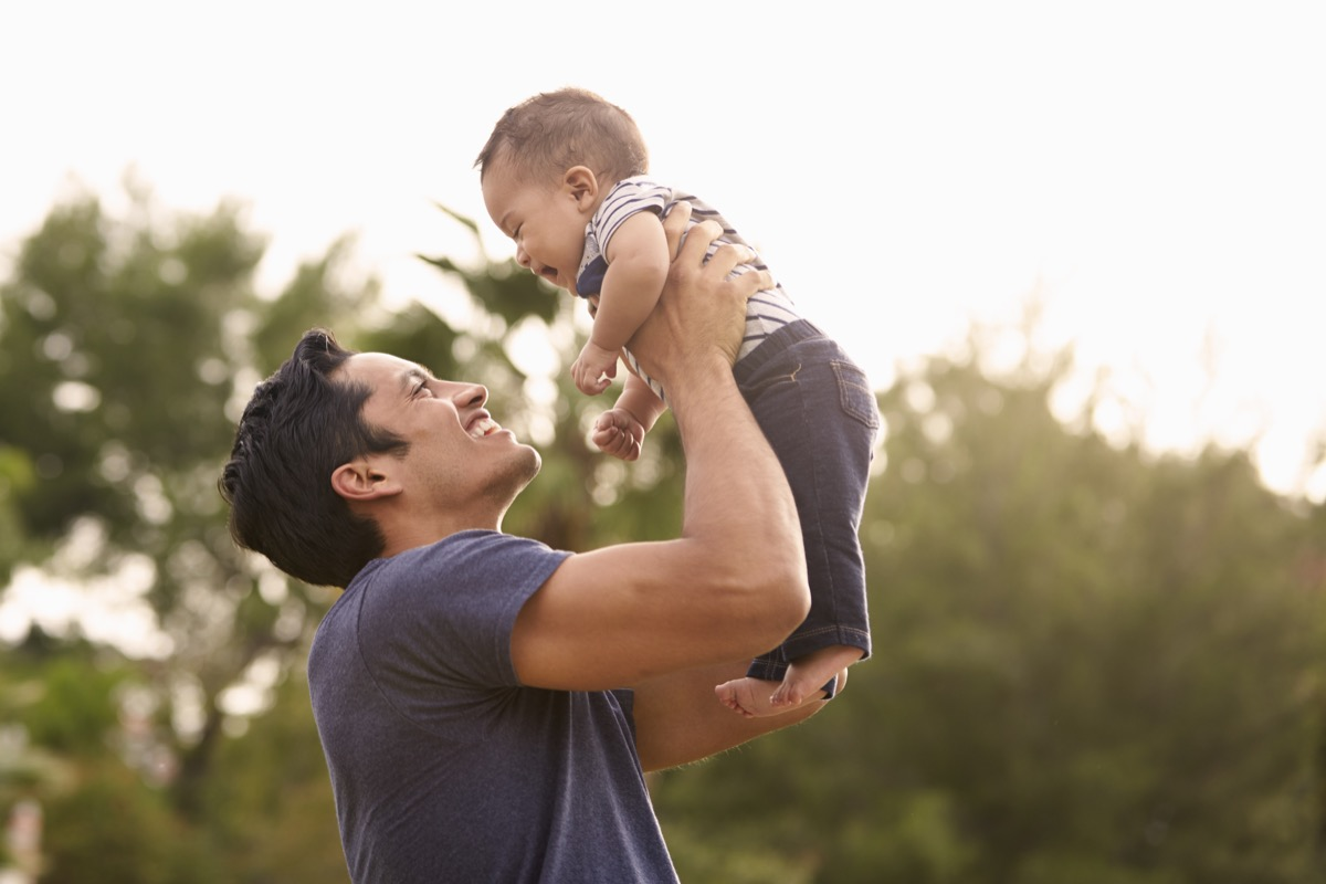 father holding his baby in the air with a smile on his face
