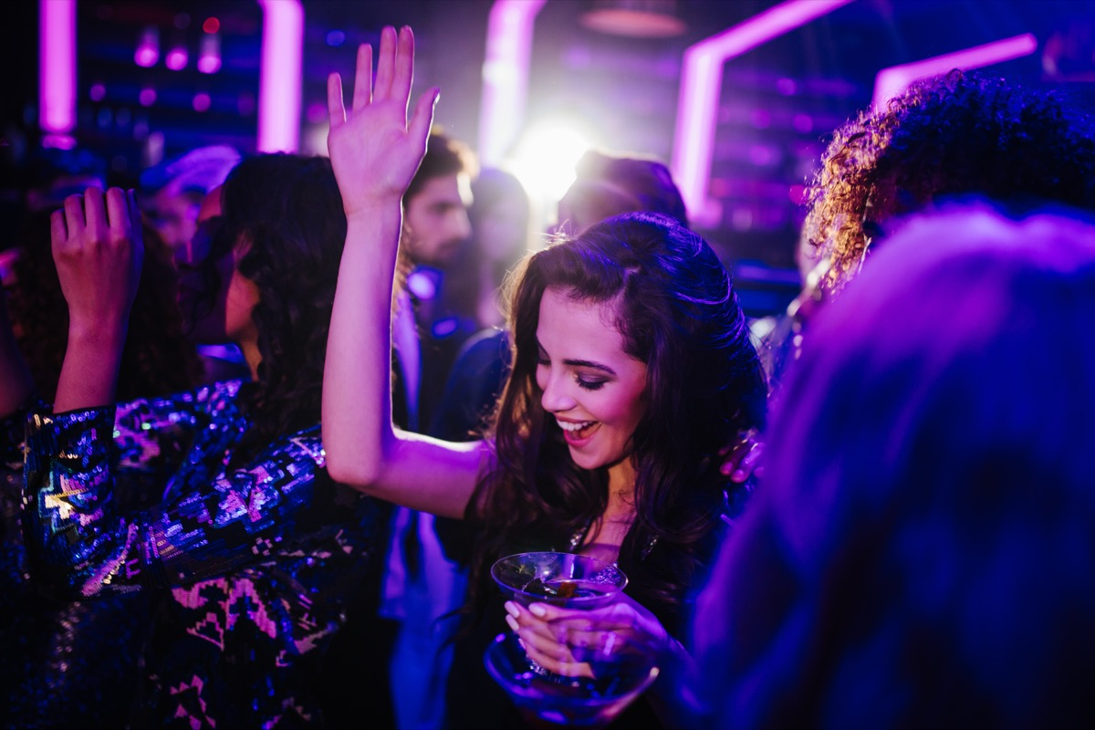 happy young adult woman dancing with her friends in a night club holding a cocktail in hand