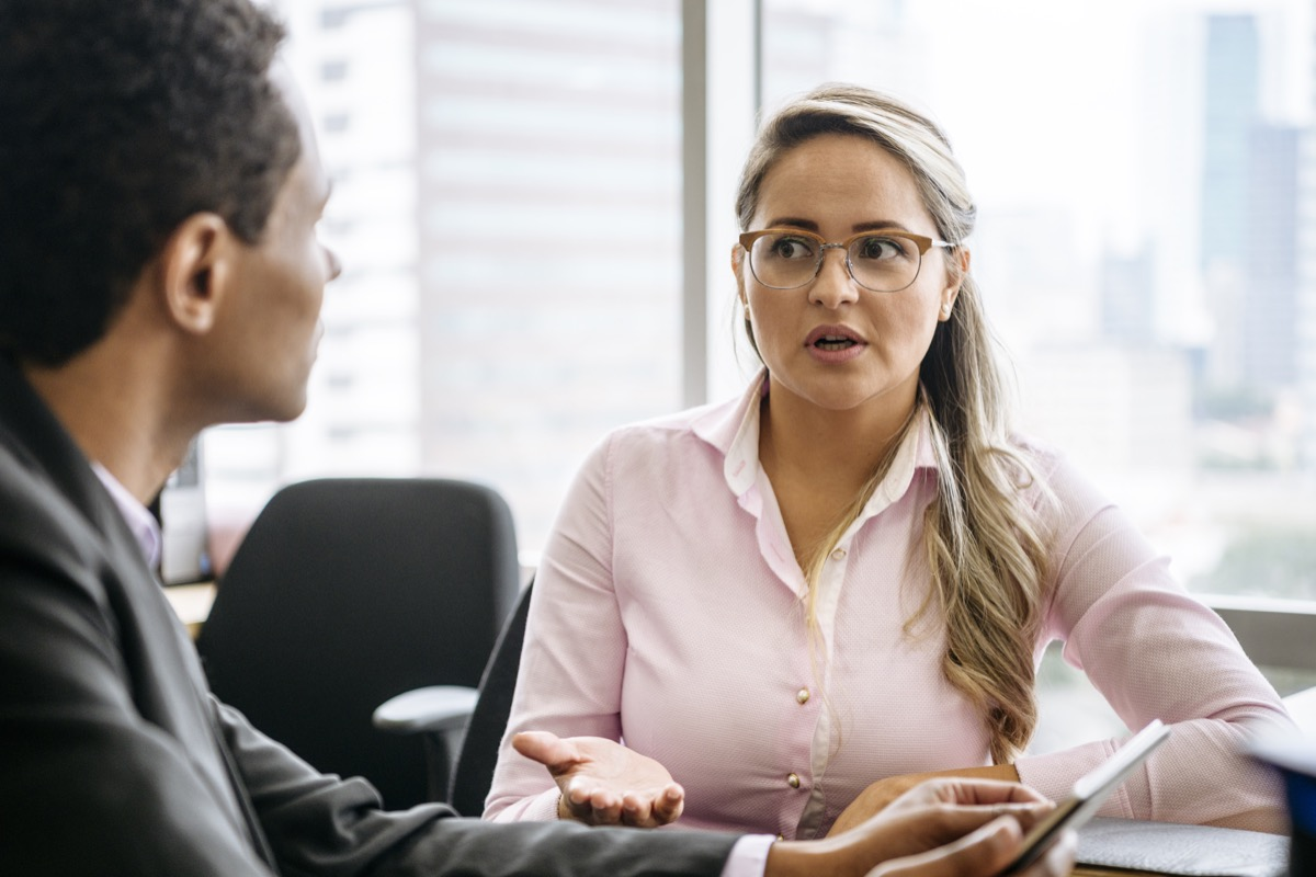 Two business people sitting in office having conversation, woman looking towards man with concerned expression