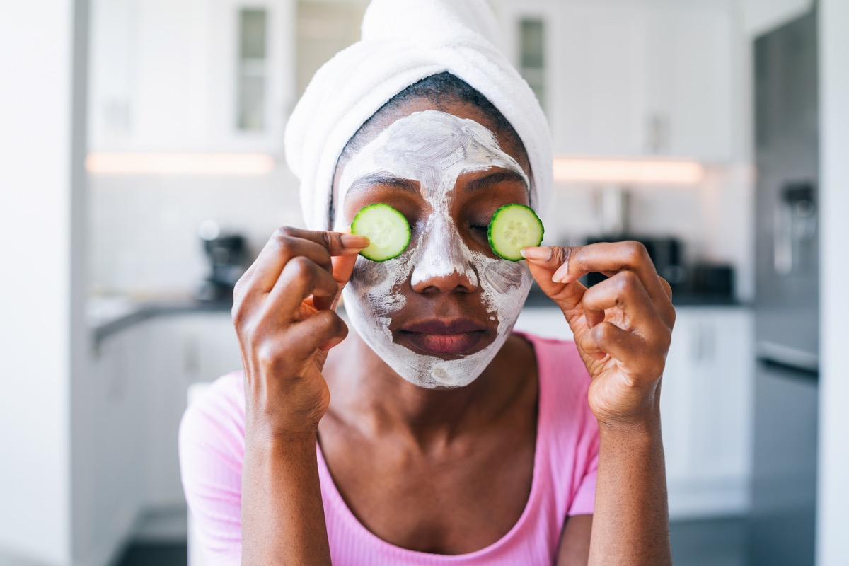 beautiful young black woman with cucumber on eyes