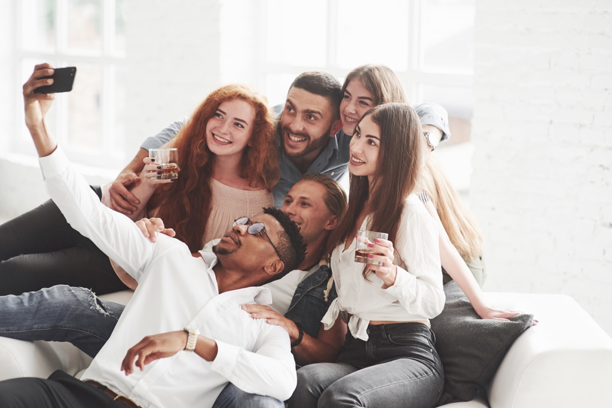 little alcohol will not be superfluous. Group of multiracial teammates having good time on their break and taking some photos.