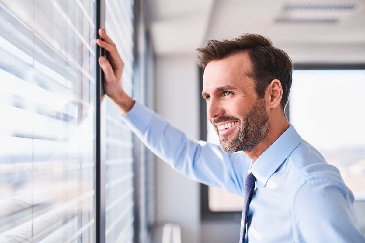 Happy man looking out of window happier life in 2019