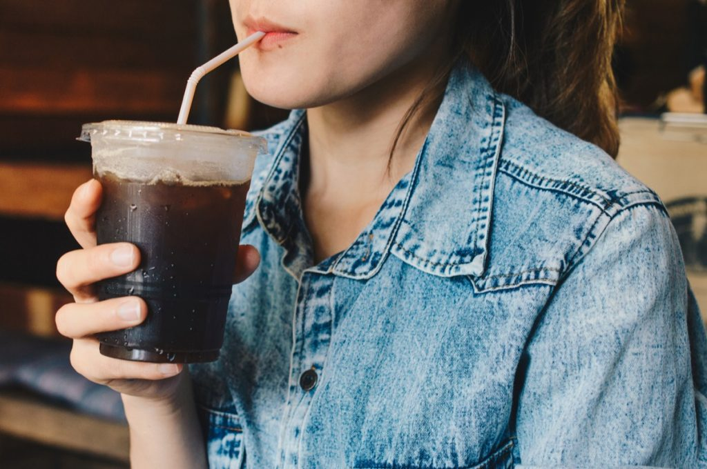 close up of woman drinking black iced coffee