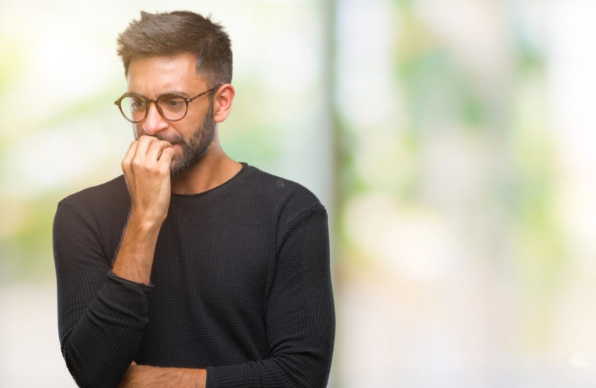 latino man biting his nails and looking nervous