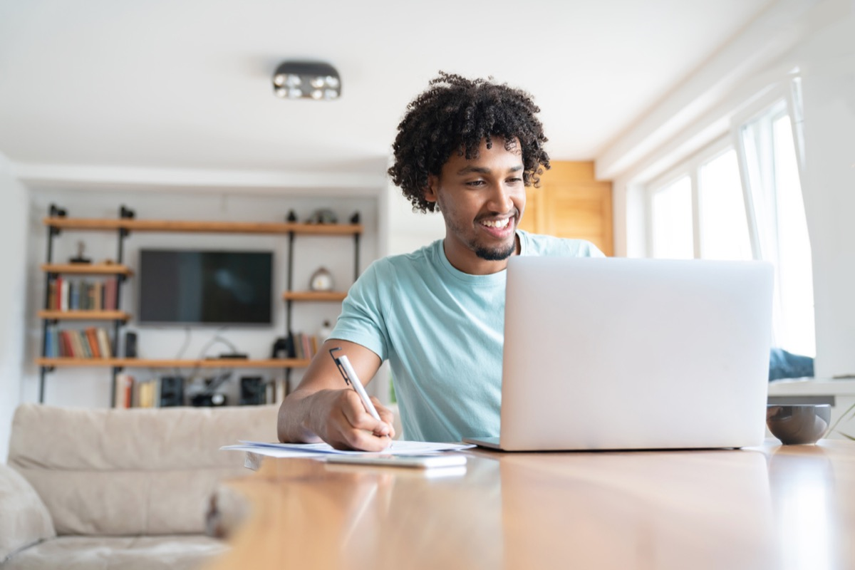 young black man smiling while writing something down and looking at his laptop