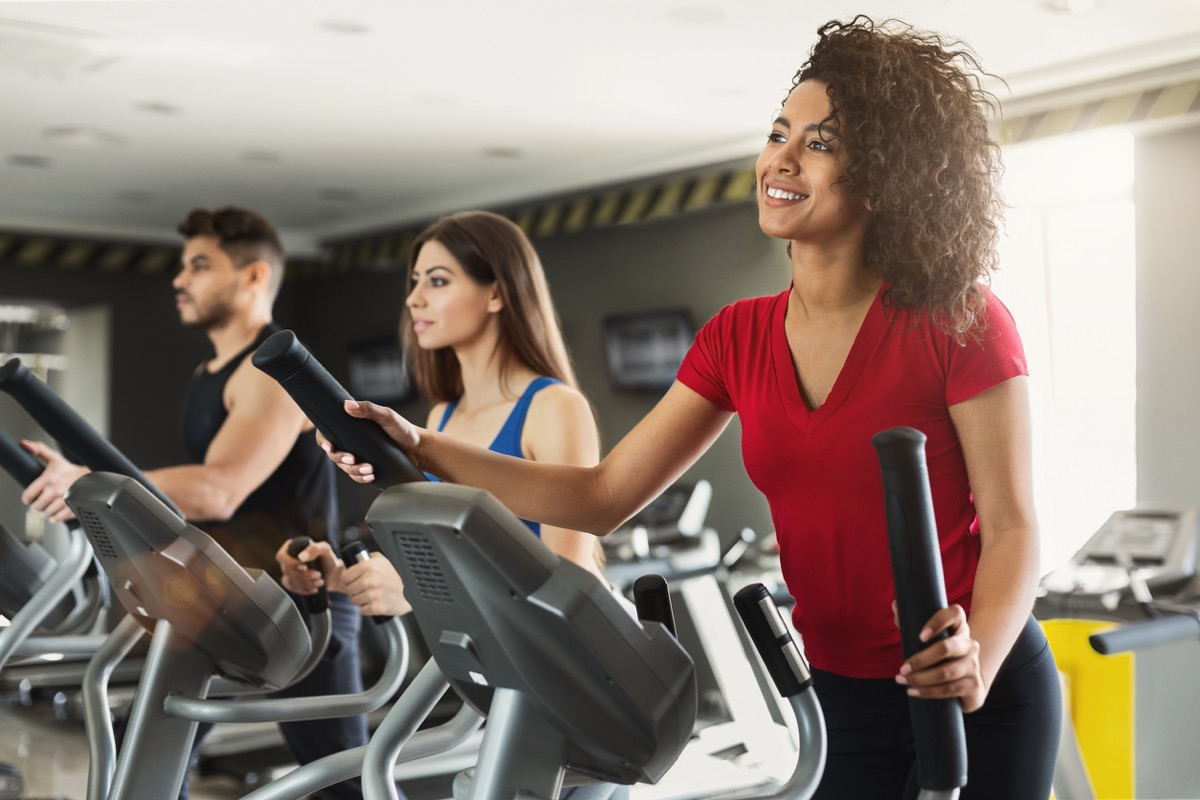 young black woman exercising on the elliptical at the gym with two other young people in the background
