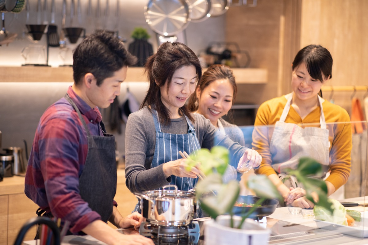 asian teacher and students making food at cooking class