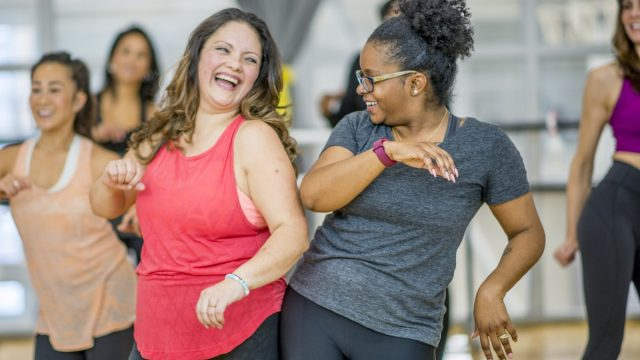 white woman and black woman dancing together at an exercise class