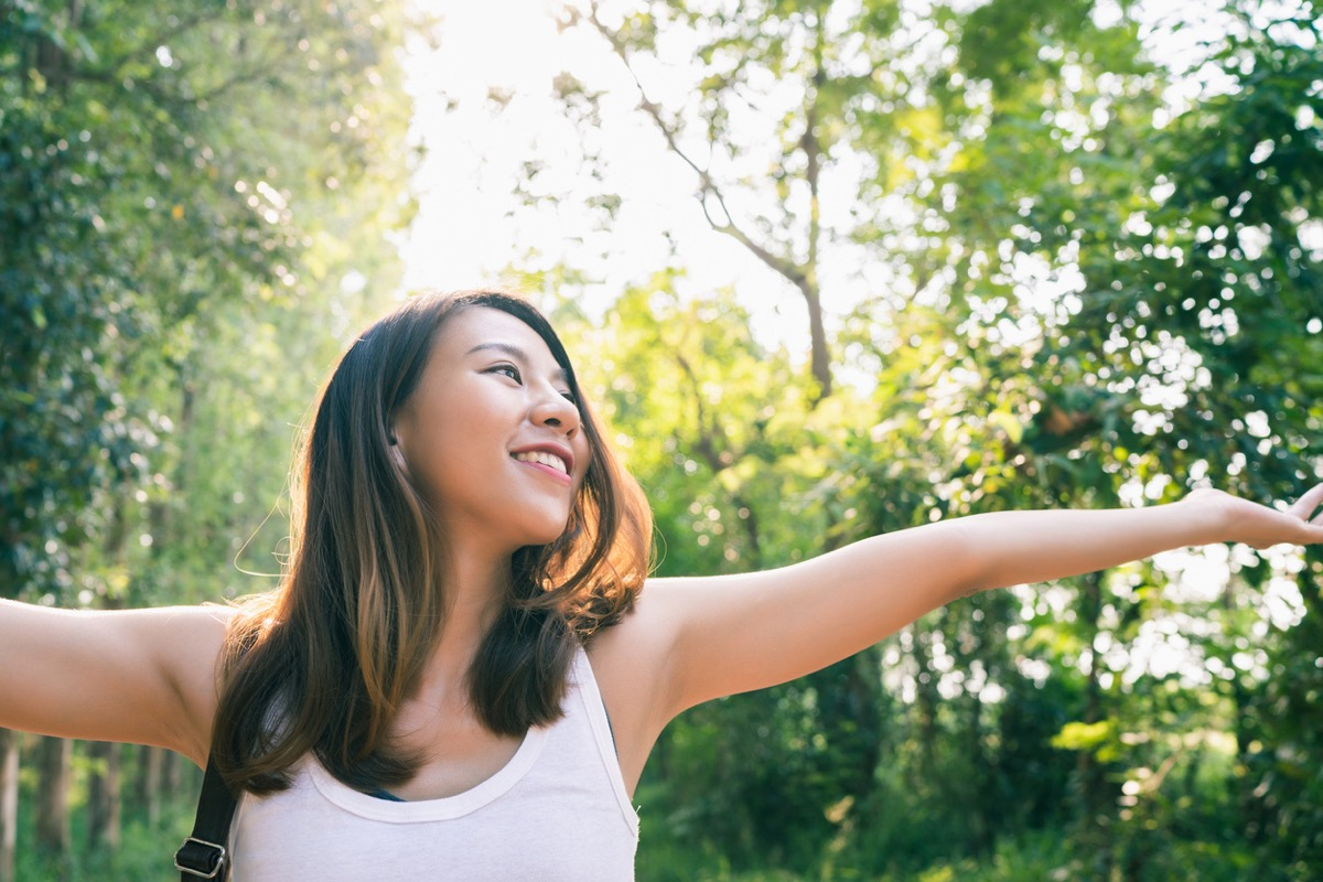 young asian woman with her arms out in a forest