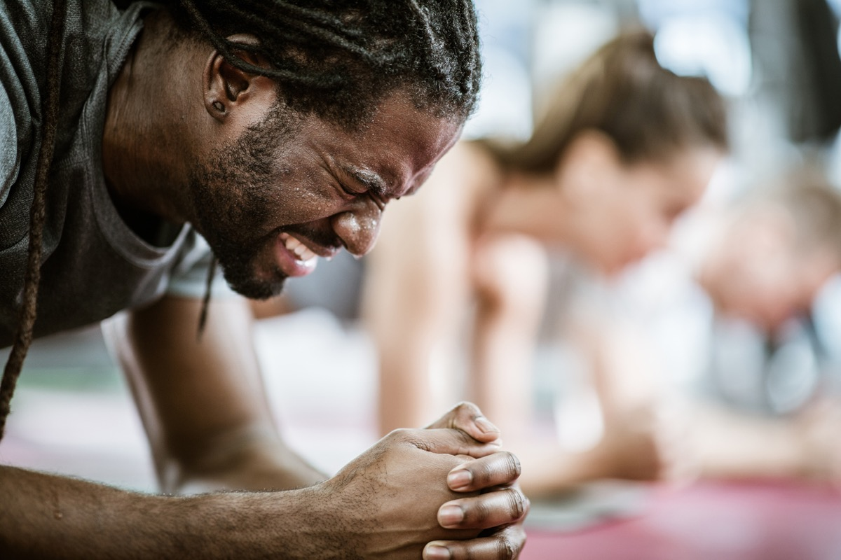 close up of black man sweating while doing a stretch at the gym