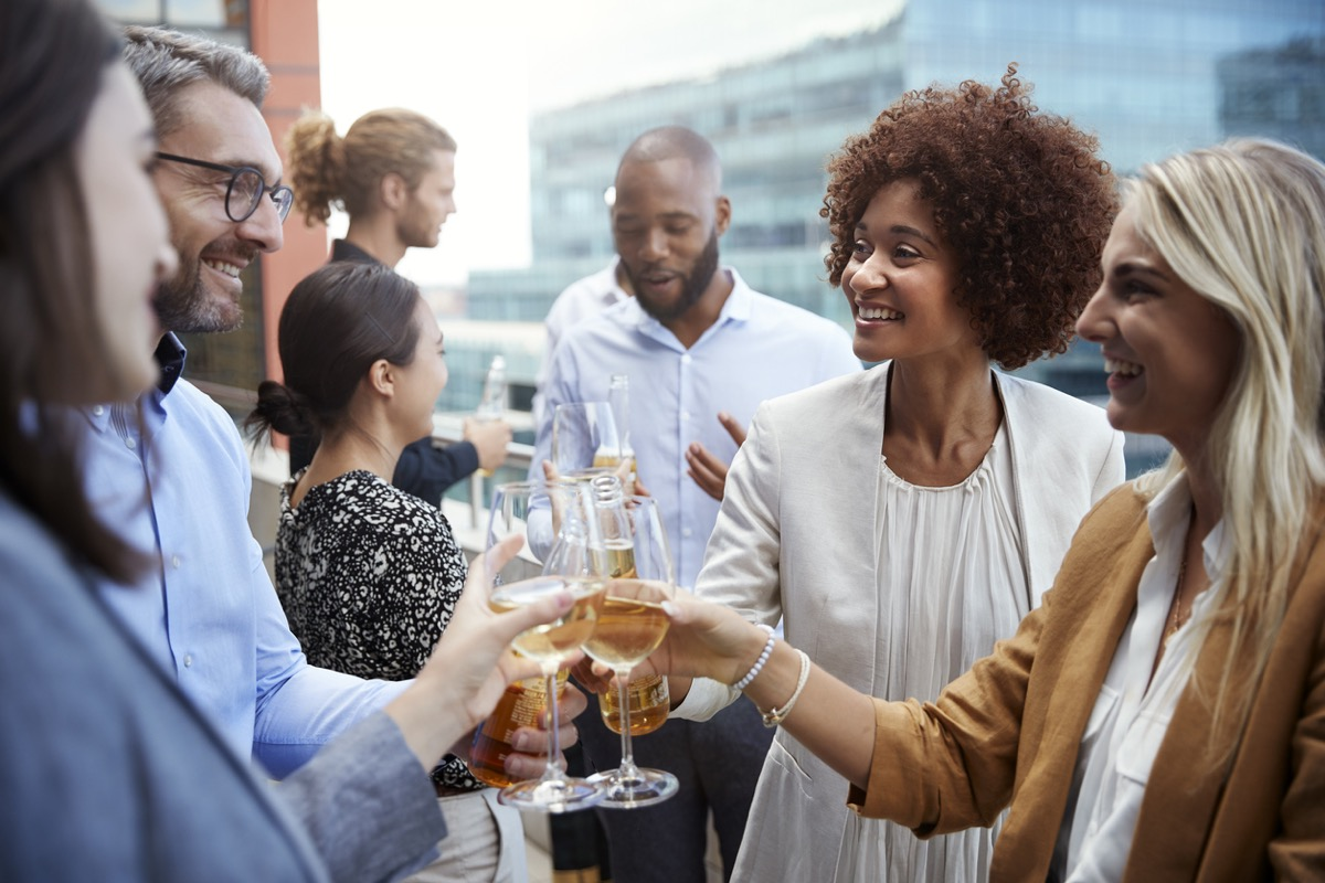 men and women who work together toasting beer and wine outside