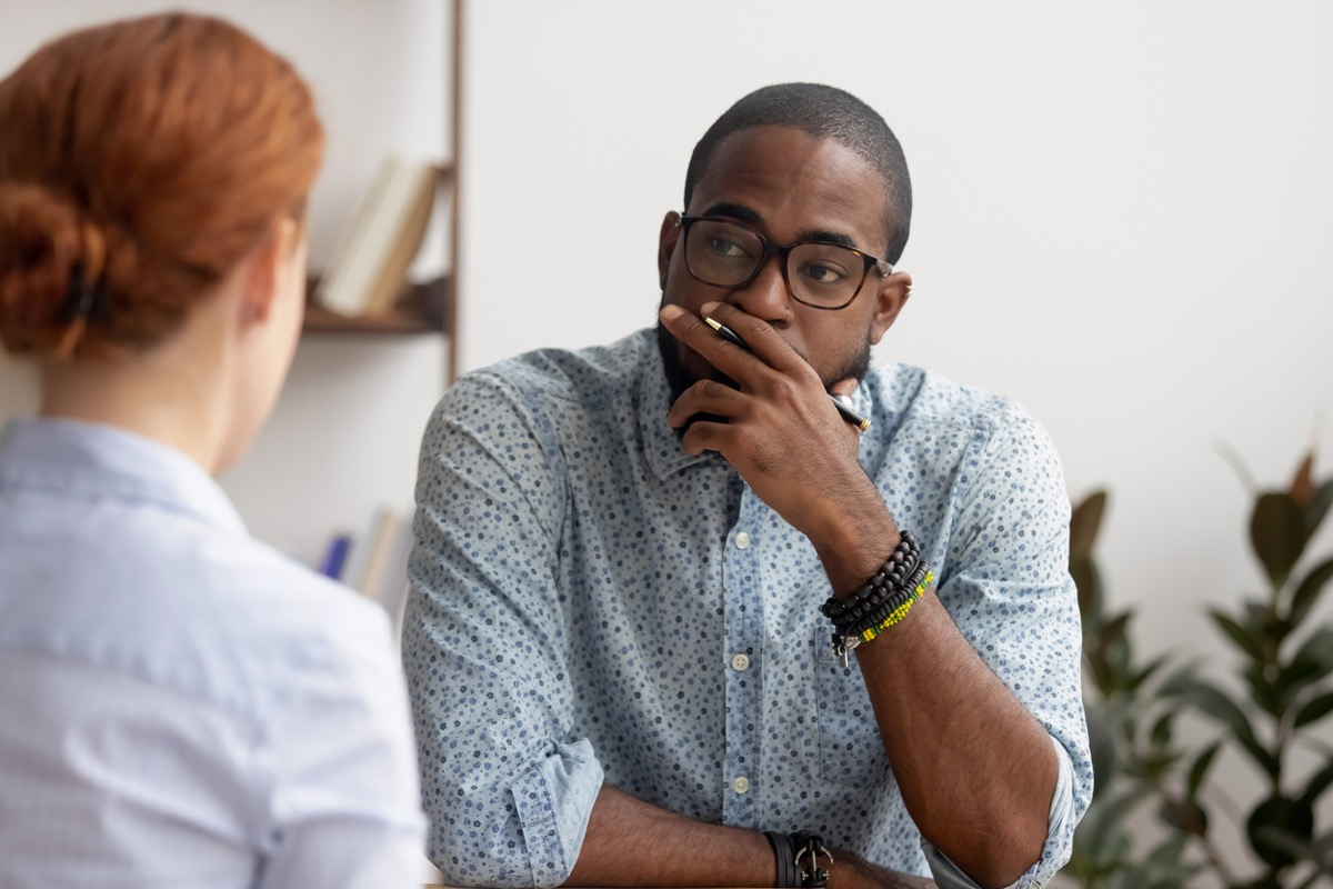 black man meeting with white redhead woman in an office