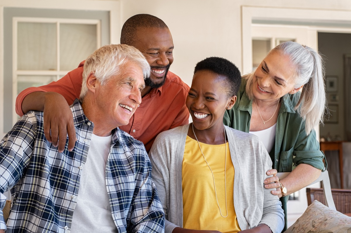 older white couple and older black couple laughing together